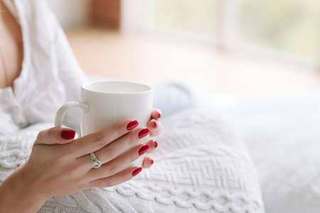 Favourite comfort drink. Morning ritual. Woman hands with cup of hot beverage. Banco de Imagens - 117037783