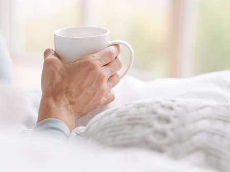 Wake up drink. Man holding white cup of hot morning beverage.