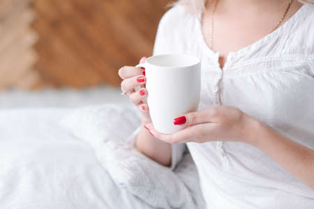 Wakening beverage. Woman in bed holding white cup of hot morning drink. Imagens