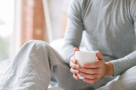 Favourite comfort beverage. New day morning. Man sitting holding cup of hot drink. Stock Photo