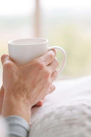 Morning coziness. Tea in man hands. Relaxing with cup of favorite drink.