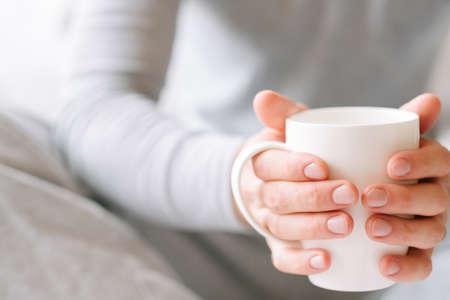 Morning coziness. Man in pyjamas holding white cup of favorite drink. Banco de Imagens