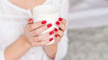 Getränk aufwachen. Frau manikürte Hände mit weißer Tasse heißem Morgengetränk. Standard-Bild