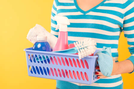 Home cleaning products. Housekeeping concept. Woman holding basket with basic supplies set.
