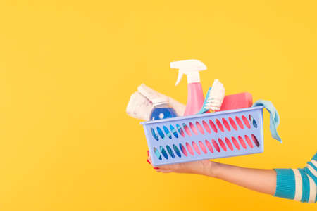 Home cleaning products. Housekeeping concept. Hand holding a basket with supplies. Copy space on yellow background. Stock Photo