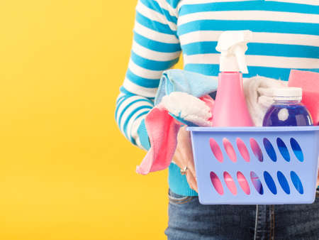 Cleaning concept. DIY home cleanup. Woman with basket of supplies. Copy space on yellow background. Stock Photo