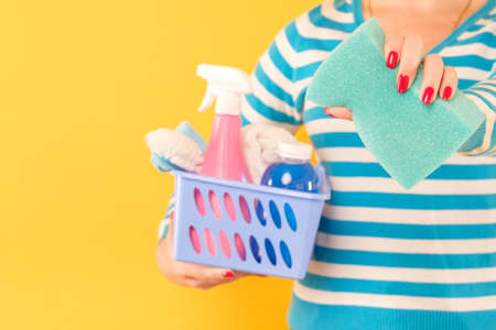 Home cleaning concept. Cleanup services. Woman holding basket of supplies and sponge. Copy space on yellow background.