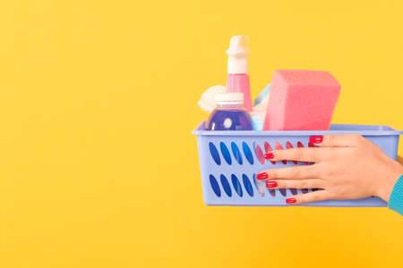 Cleaning products shopping. Basket of supplies in woman hands. Copy space on yellow background.