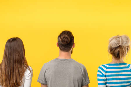 Advertising concept. Three people backview looking at imaginary object. Copy space on yellow background. Stock Photo