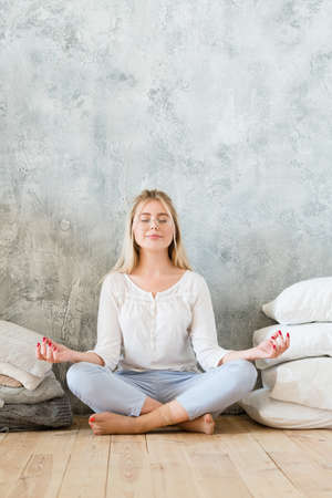Morning meditation. Lifestyle concept. Young woman sitting on floor cross legged with mudra hands. Copy space on grey background.