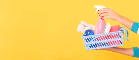 Cleaning concept. DIY home cleanup. Woman with basket of supplies pointing atomizer. Copy space on yellow background. Stock Photo