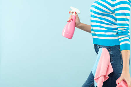 Household chores. Organized housewife. Woman holding atomizer and sponge with cloth in pocket. Copy space on blue background. Stock Photo