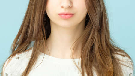 Female plumpy lips. Beauty concept. Girl with long brown hair and clean fresh skin looking toward camera.
