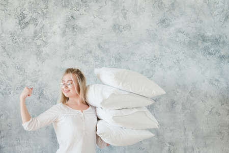 Pillow cleaning. Organized housewife. Woman holding pile of pillows and showing biceps.