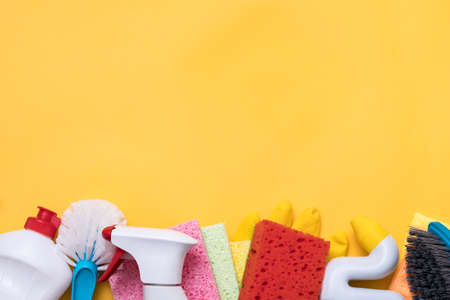 Cleaning supplies shopping. Products assortment. Copy space on yellow background. Stock Photo