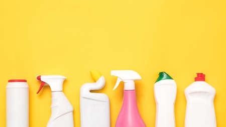 Suministros de limpieza de la casa sobre fondo amarillo. Fila de botellas de plástico con espacio de copia. Foto de archivo