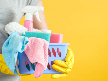 Home cleaning concept. Woman holding basket with basic set of supplies. Copy space on yellow background.