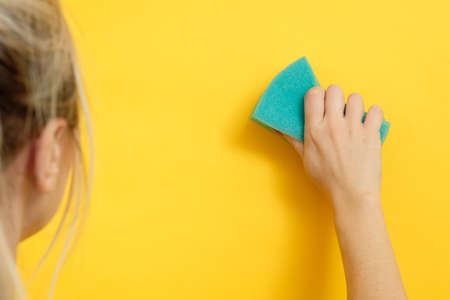 Home cleaning. Safe and super clean. Woman wiping imaginary spot. Yellow background. Stock Photo