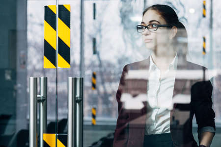 Business millennial portrait. Thoughtful young woman in glasses standing in office workspace.