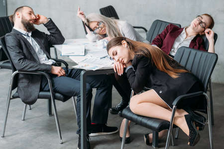 Tired corporate personnel. Overworking concept. Business team members sleeping on desk and chairs. Stockfoto