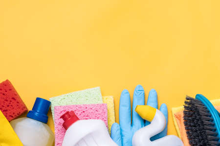 Home cleaning products on yellow background. Assorted variety of supplies beneath copy space. Stock Photo