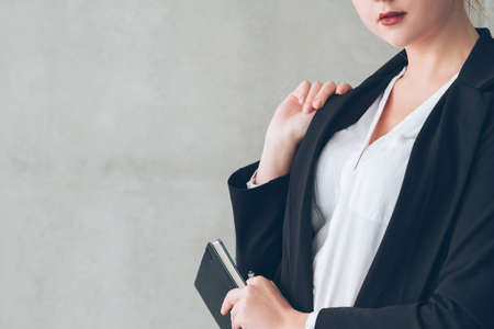 Business woman portrait. Confident female with hand at lapel holding day planner. Copy space on grey background.