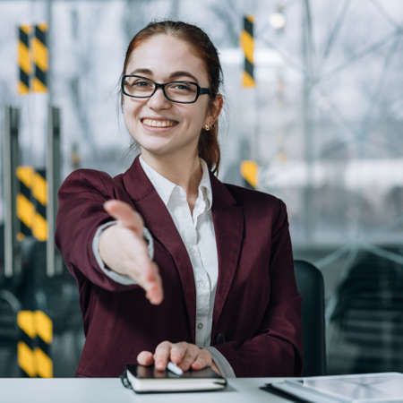 Friendly employee portrait. Job hiring. Young smiling intern in glasses extending welcoming hand. Stock Photo
