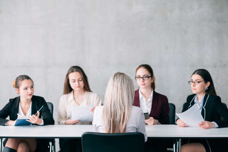 Job interview. Staffing and hiring. Blonde female talking to recruiter team members.
