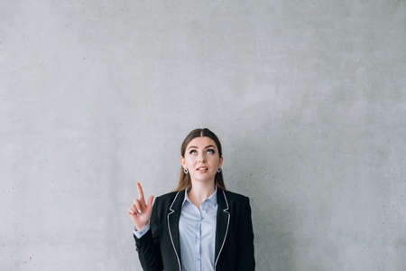 Recruiting. We are hiring. Business lady pointing at virtual sign. Copy space on grey background. Stock Photo
