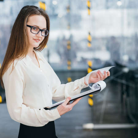 Confident teamlead at office workspace. Successful career. Young business woman in glasses hold documents. Imagens