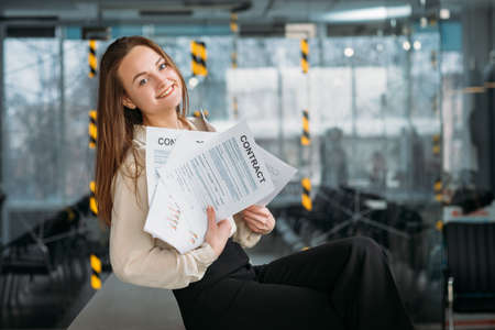 Corporate lawyer at workplace. Smiling young woman sitting on desk with handful of contracts. Zdjęcie Seryjne