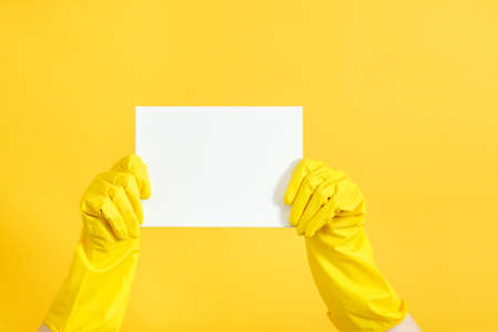 Home cleaning to do list. Hands in rubber gloves holding blank paper mockup. Copy space on yellow background.