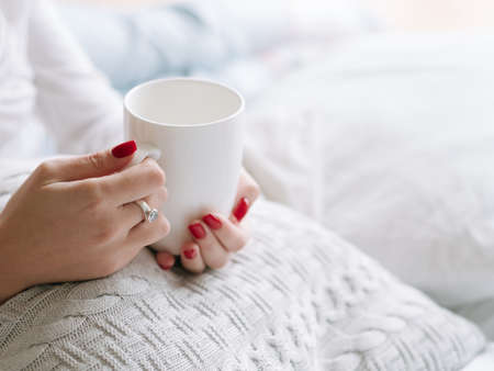 Wake up drink. Woman hands with white cup of hot morning beverage. Banco de Imagens - 117538775