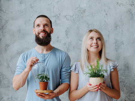 Plant care. Nature protection concept. Smiling environmentally friendly couple with houseplants.