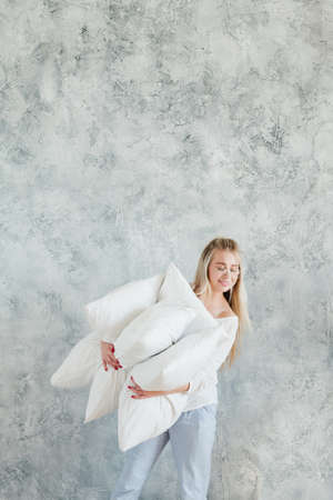Feather pillows. Housewife choice. Smiling young woman holding comforting pile. Copy space on grey background.