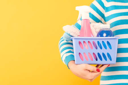 Home cleaning products. Housekeeping concept. Woman holding basket with cleanup supplies. Copy space on yellow background. Stock Photo