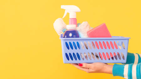 House cleanup. Basic cleaning set. Hands holding basket of supplies. Copy space on yellow background.