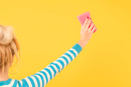Cleaning concept. DIY home cleanup. Woman with sponge wiping imaginary spot. Stock Photo
