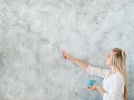 Woman in leisure clothing pointing to the left. Copy space for text on grey background. Cup of tea in hand