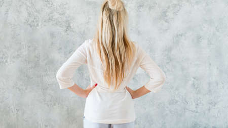 Taking decision concept. Blonde woman hands on hips backview. Copy space on grey textured background. Stock Photo