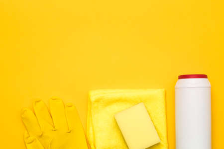Home cleaning supplies. Row of products on yellow background beneath copy space. Stock Photo