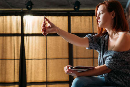 Fine artist sketching. Studio workspace. Female painter measuring virtual object holding sketchbook.