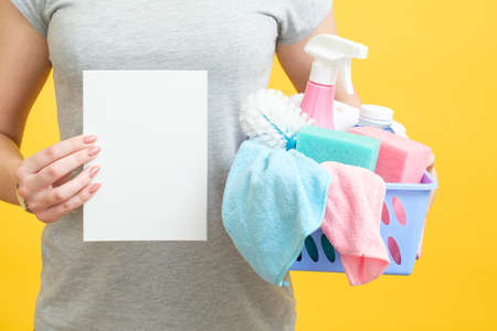 House cleaning checklist. Torso holding paper mockup and basket of supplies. Yellow background.