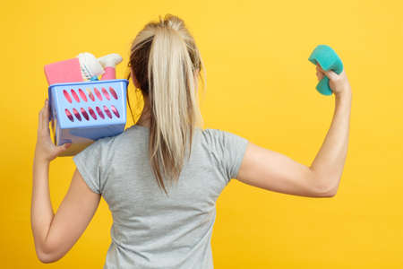 Organized housewife. Housekeeping concept. Woman with basket of cleaning supplies showing biceps on yellow background.
