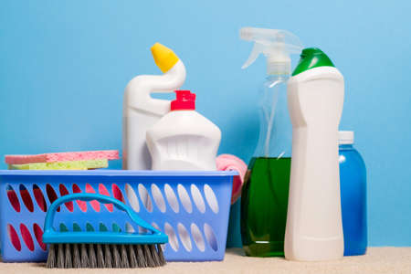 Home cleaning products background. Assorted variety of supplies on blue backdrop.