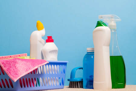 Home disinfection. Cleaning products assortment on blue background.