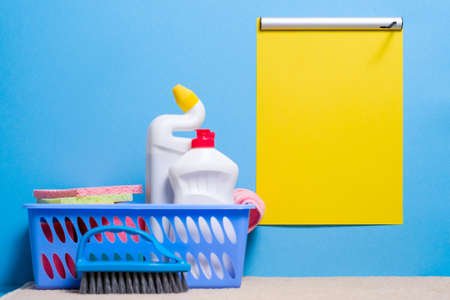 Cleaning products background. Plastic basket with supplies with yellow checklist mockup on blue backdrop. Stock Photo