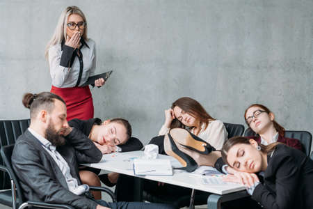 Tired corporate personnel. Overworking concept. Colleague looking at team members sleeping on desk and chairs.