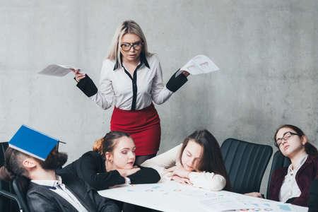 Accounting period overworking. Business team members sleeping on desk. Shocked colleague alarming. 写真素材