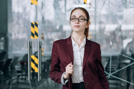 Company employee portrait. Confident headhunter in glasses with hand at lapel. Office workspace.